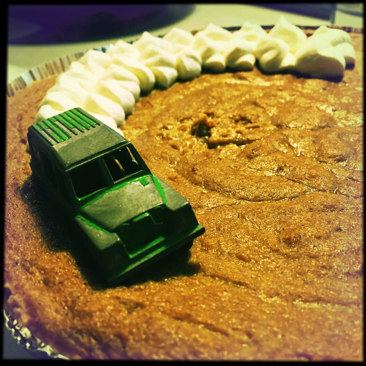 a photo of a pumpkin pie with a small toy car fishtailing across it, leaving a trail of whipped cream smoke in its wake